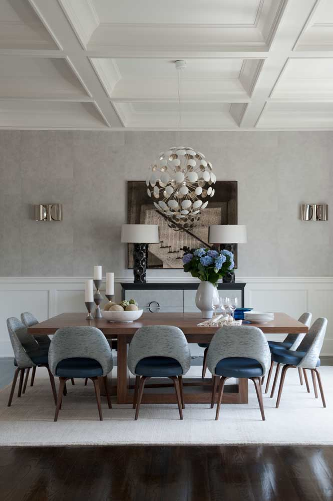 Sala de jantar grande com mesa de dez lugares. Repare que o tapete cobre toda a extensão da mesa