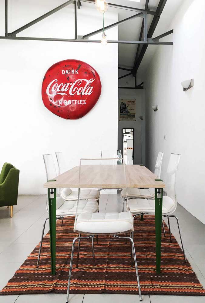 As cadeiras de acrílico reforçam o estilo clean e moderno da sala de jantar