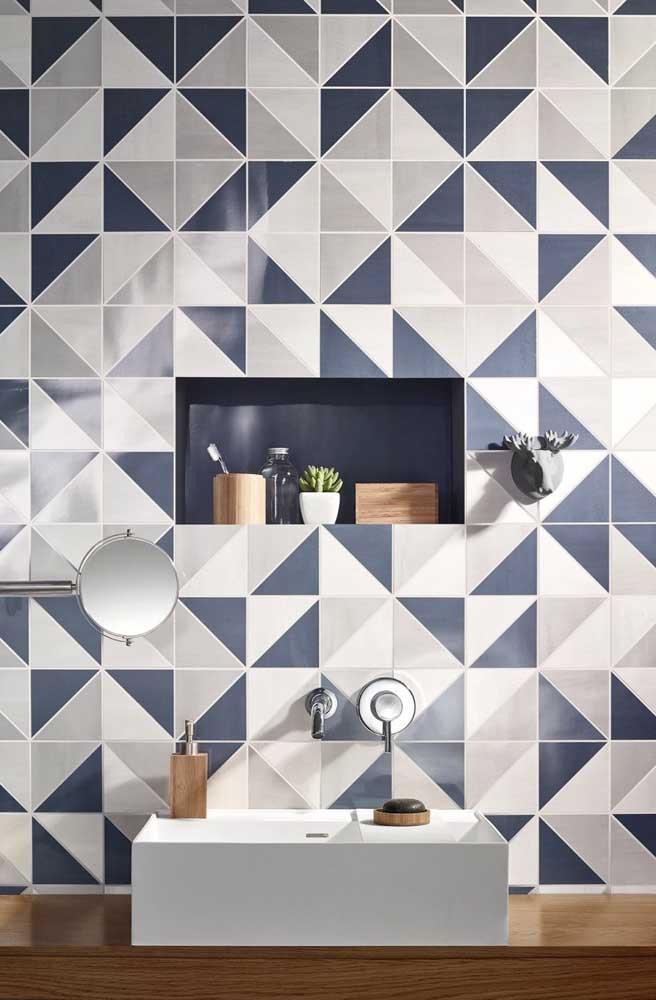 O nicho azul ganha destaque junto a parede estampada do banheiro