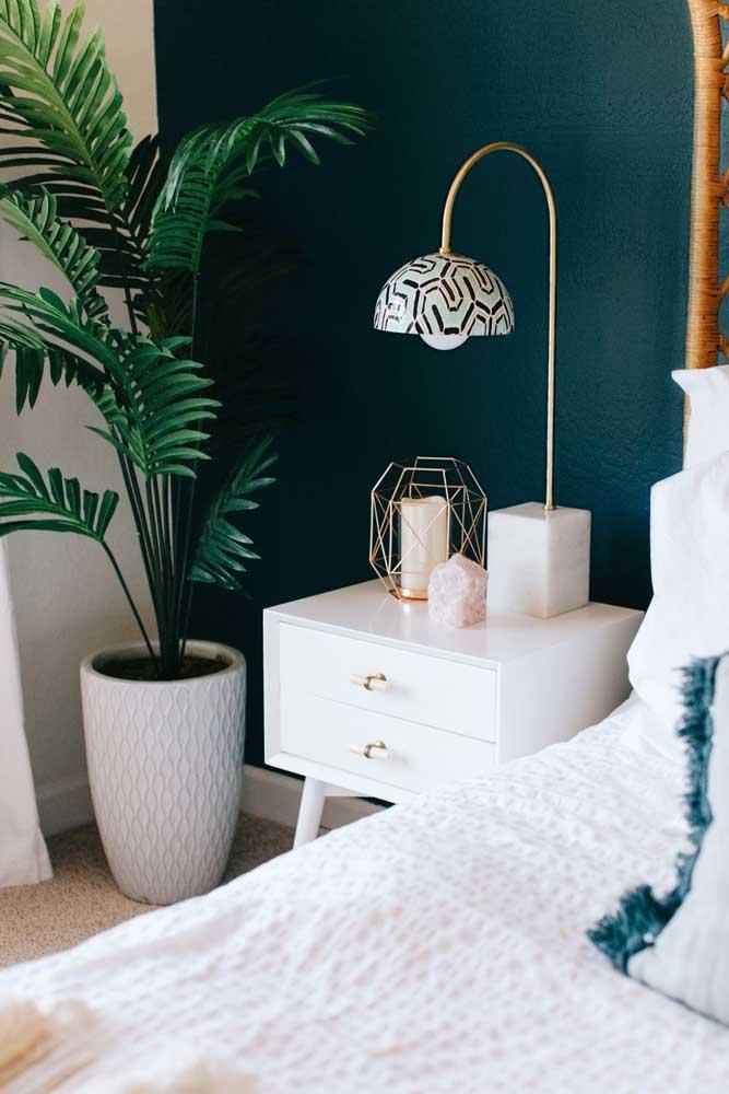 A parede azul do quarto contrasta com as folhas verdes e o vaso branco da ráfia