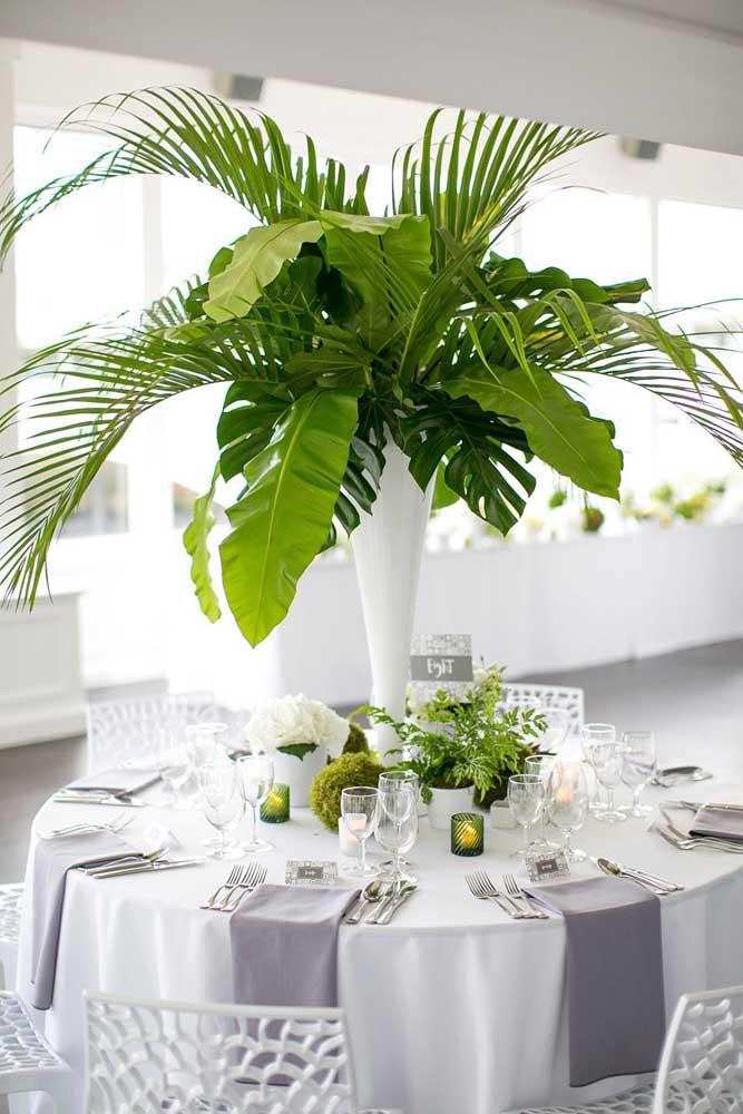 Um arranjo de mesa em estilo tropical e bem diferente. Aqui, a opção foi por folhas de ráfia e de costela de adão