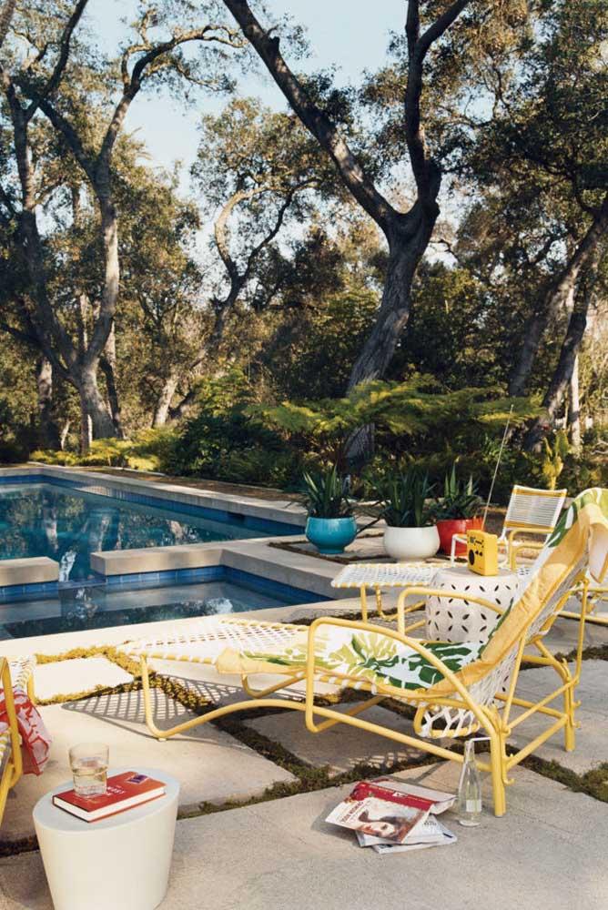 Área de lazer com piscina rodeada de árvores. As espreguiçadeiras deixam o lugar ainda mais convidativo