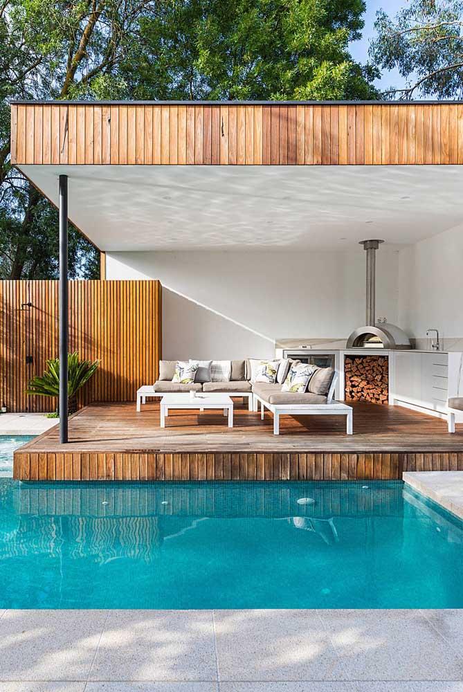 A madeira traz conforto para a área de lazer com piscina e churrasqueira