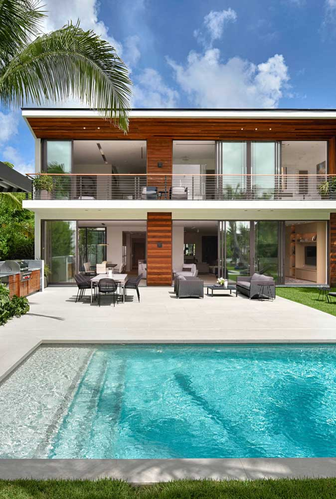 Nessa casa sobrado, a área de lazer traz uma piscina que se assemelha a uma prainha