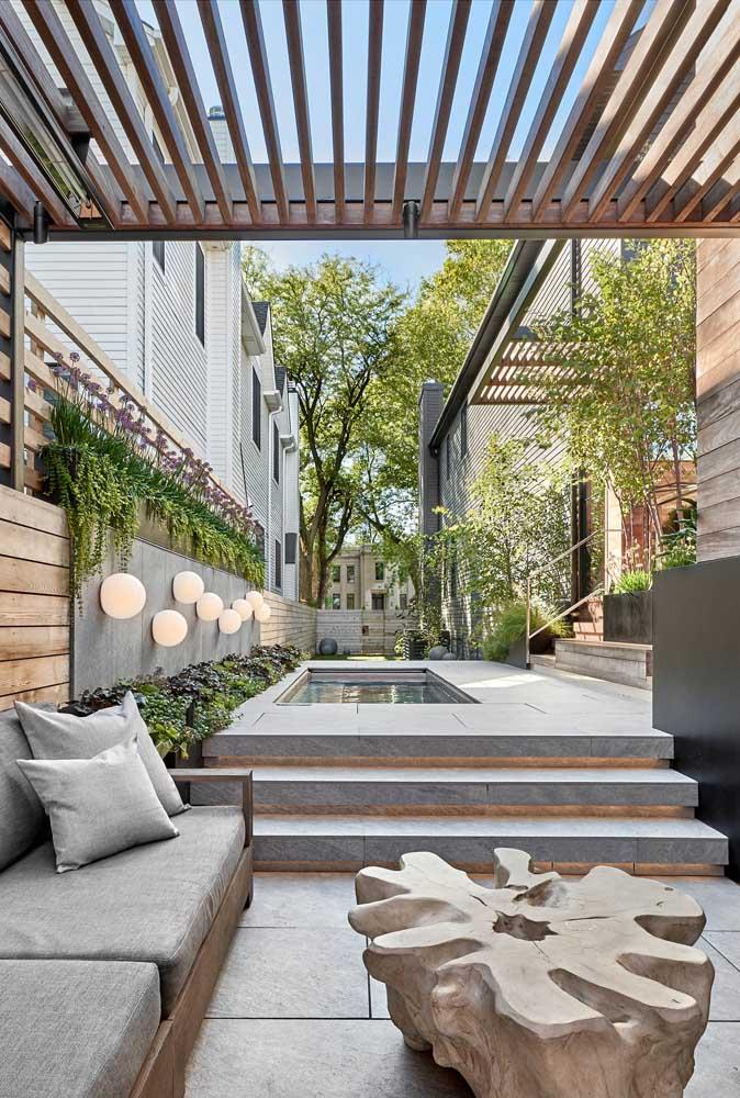 Área de lazer com piscina, espaço de convivência e jardim vertical