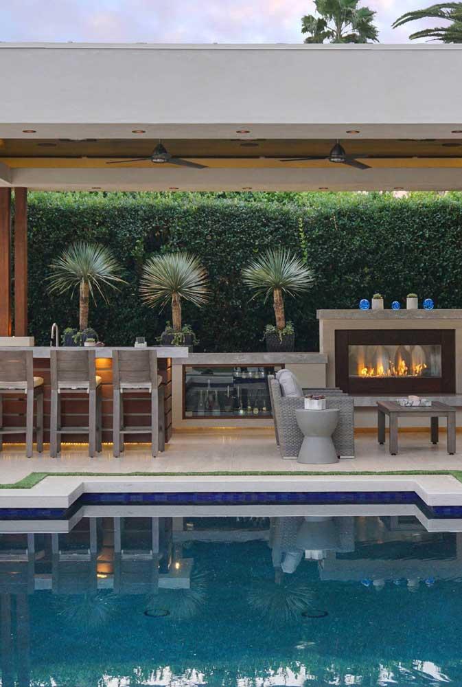 Área de lazer com piscina e espaço gourmet moderno, com direito a forno, bar e lareira