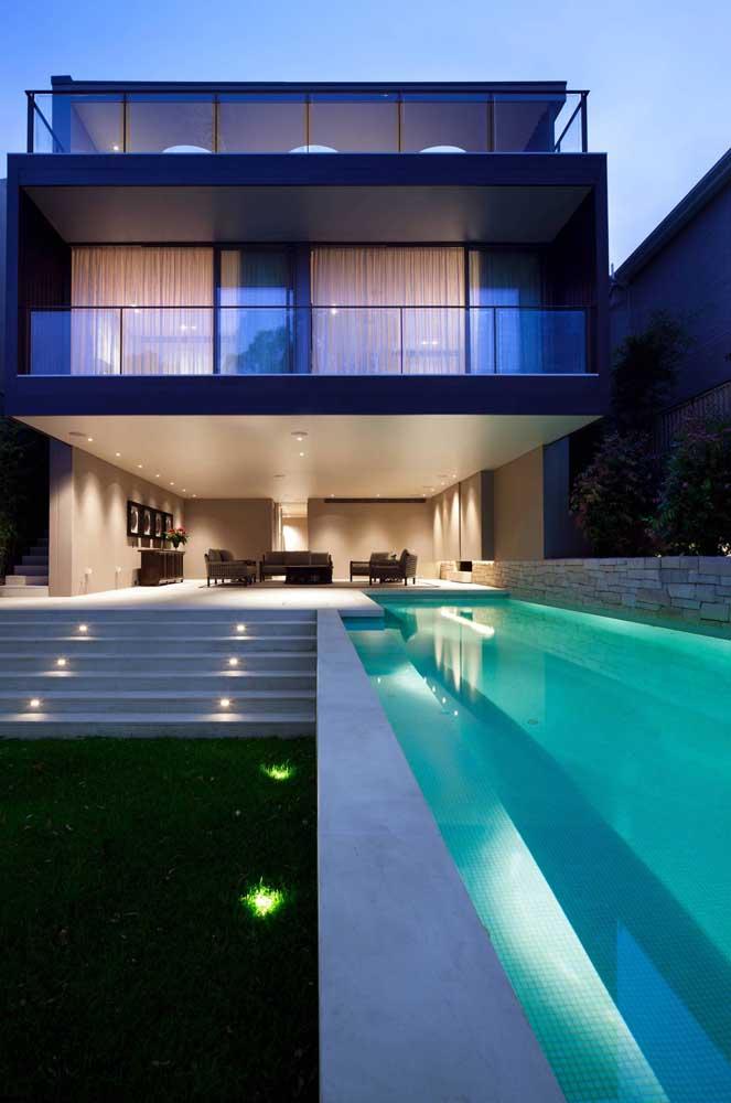Área de lazer com piscina retangular e iluminada
