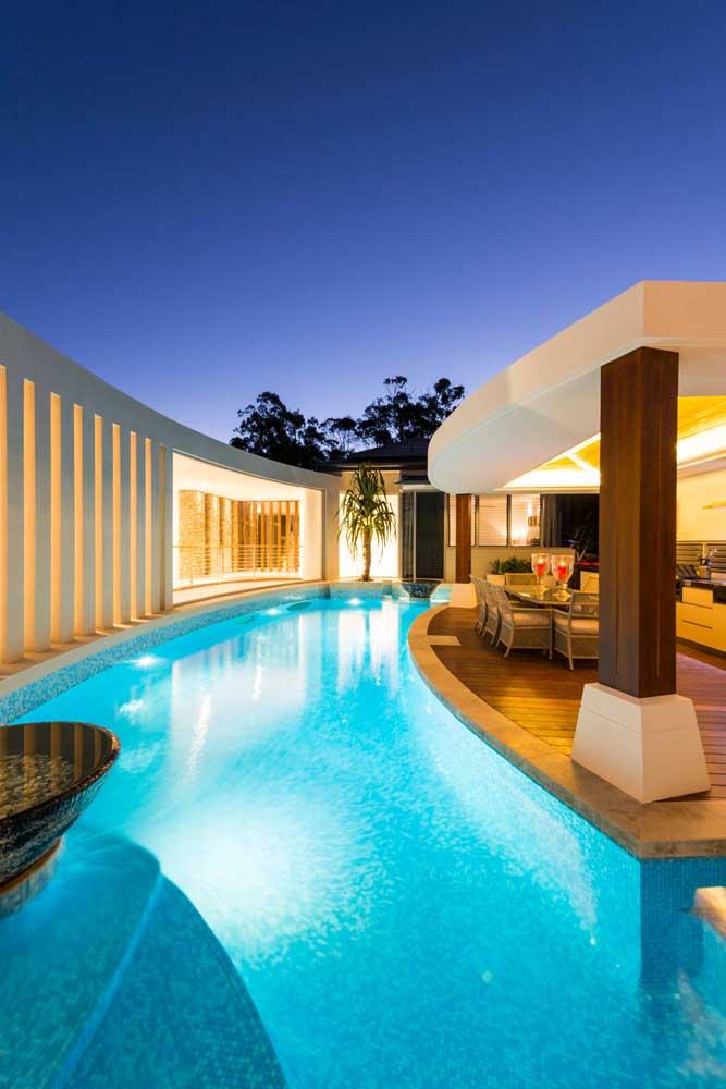 A iluminação noturna deixa a área de lazer com piscina ainda mais aconchegante e bonita