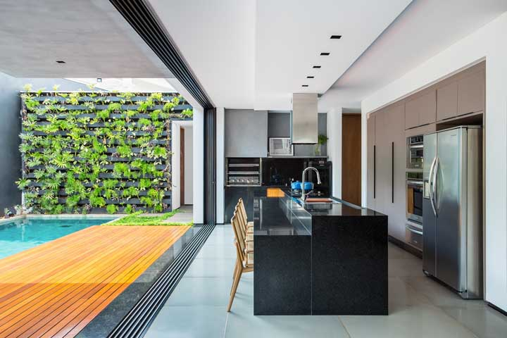 Área de lazer com piscina integrada a cozinha da casa