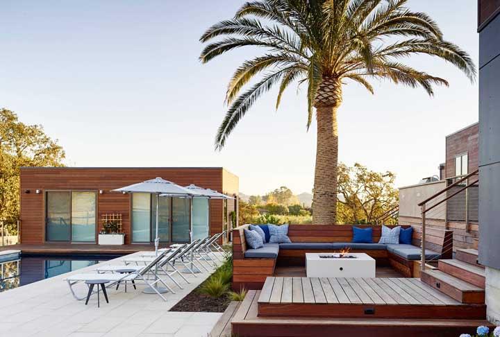 Área de lazer com piscina em local amplo e aberto. Destaque para o uso da madeira em todo o projeto
