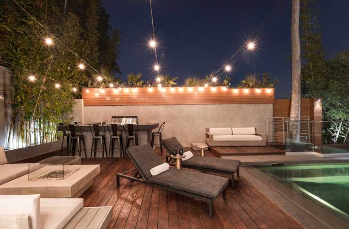 Área de lazer com piscina, churrasqueira, bar e espaço para fogueira