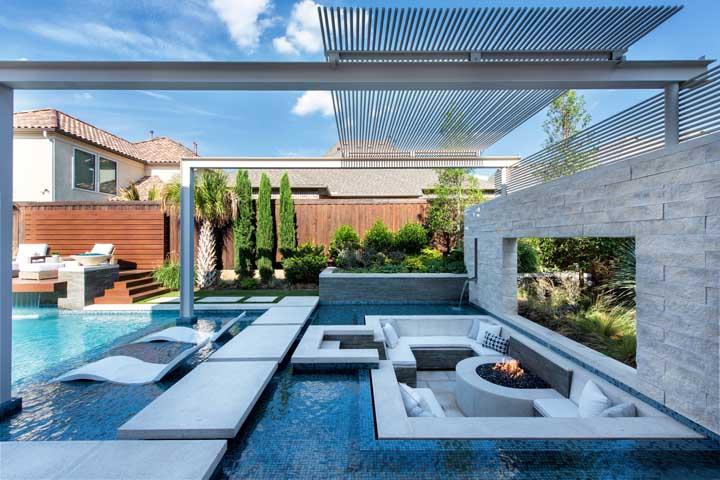Um projeto incrível de área de lazer com piscina. A área de convivência parece estar dentro da piscina, graças a borda infinita