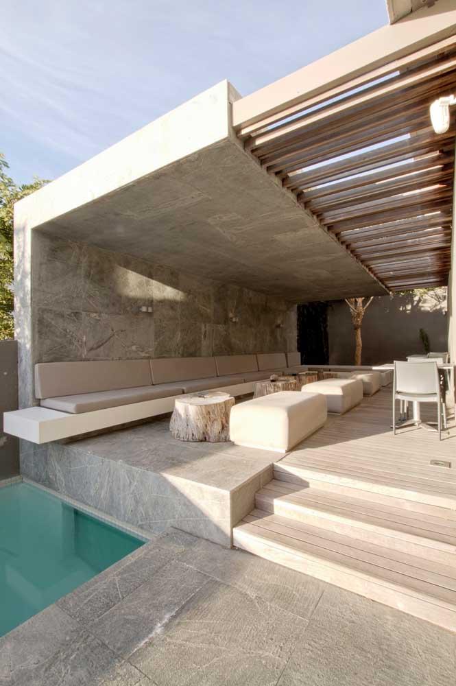 Área de lazer com piscina moderna e elegante. O piso claro fez um lindo contraste com a madeira do teto