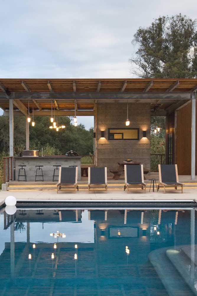 Área de lazer com piscina e churrasqueira. O projeto de iluminação permite que o espaço seja usado a qualquer momento