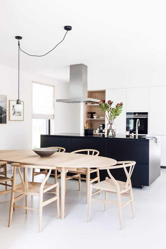Cozinha americana com sala de jantar em tons de branco e preto. A madeira entra para trazer conforto