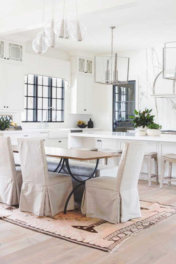 Cozinha americana com sala de jantar em estilo clássico. As cores neutras são o destaque por aqui