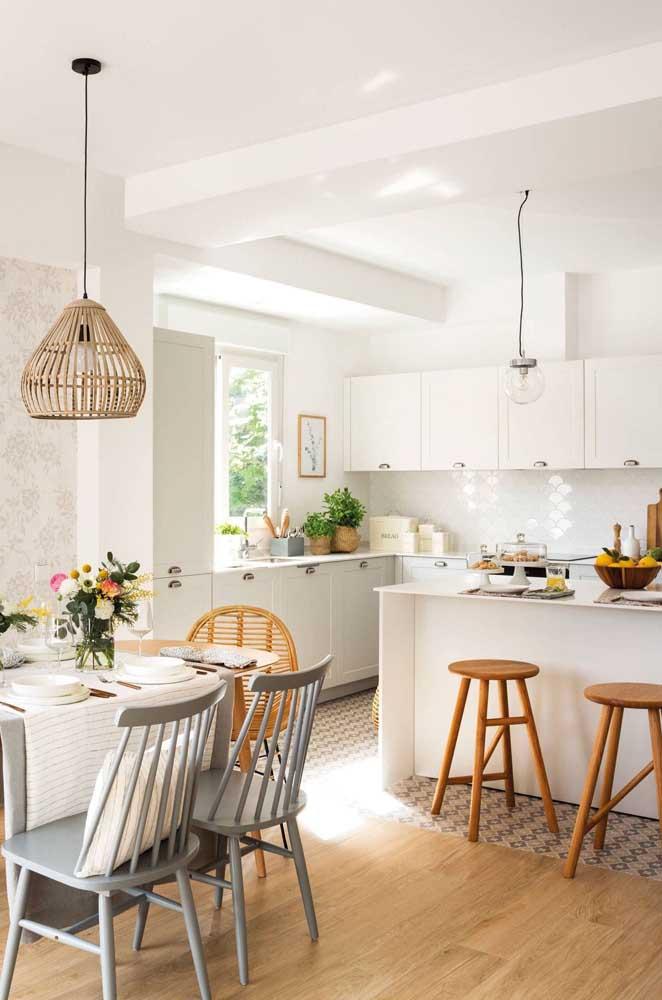 Cozinha americana com sala de jantar pequena e simples com móveis brancos e muita luz natural
