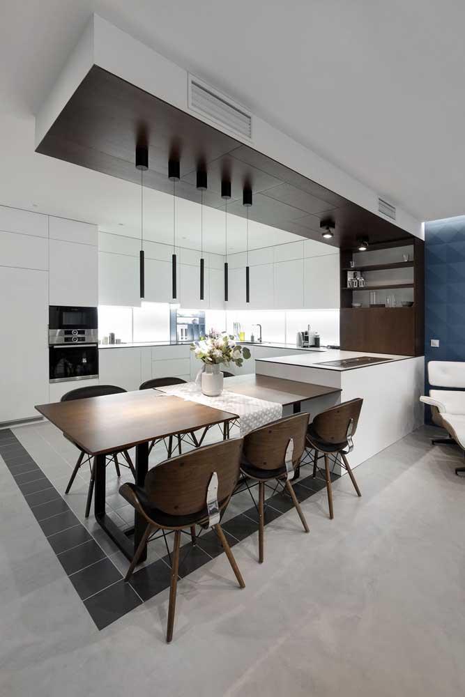 Nesse projeto, a área feita em madeira delimita o espaço entre a cozinha e a sala de jantar