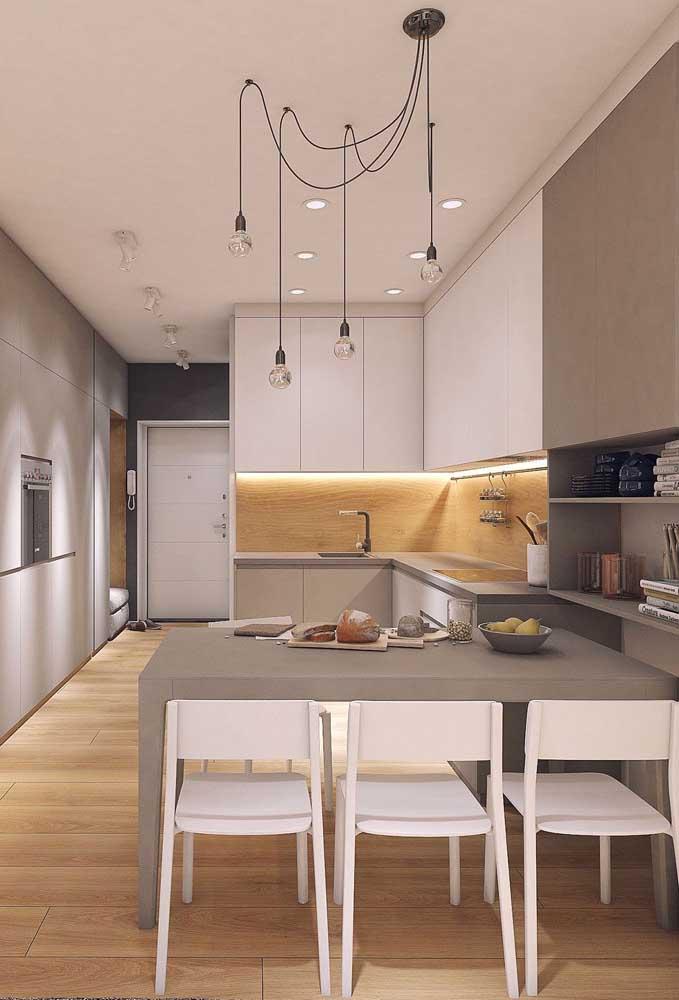 Cozinha americana com sala de jantar em estilo corredor. Repare na paleta neutra de cores que valoriza o ambiente