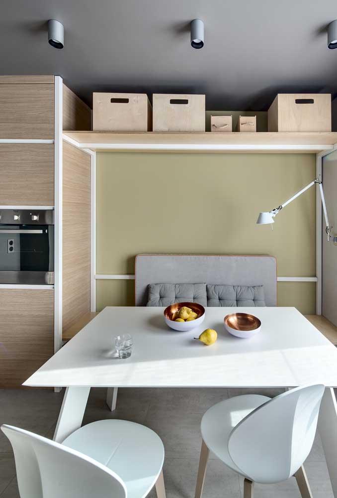 Cozinha americana com sala de jantar simples e pequena. Repare que a mesa de jantar simula um canto alemão