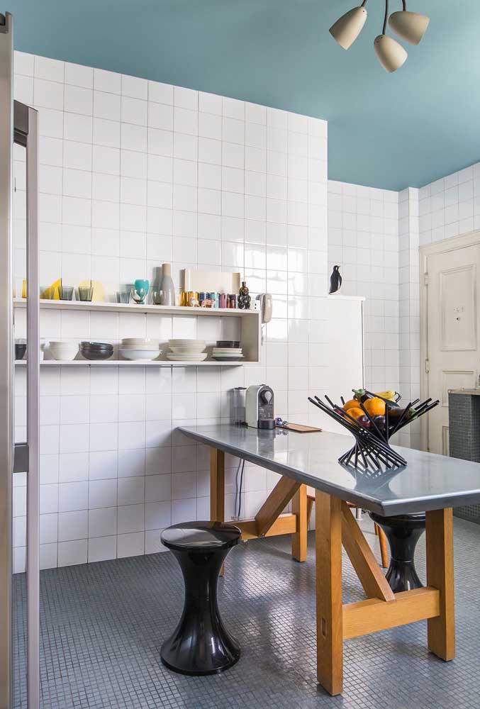 Cozinha com piso de pastilhas pequenas contrastando com o revestimento da parede