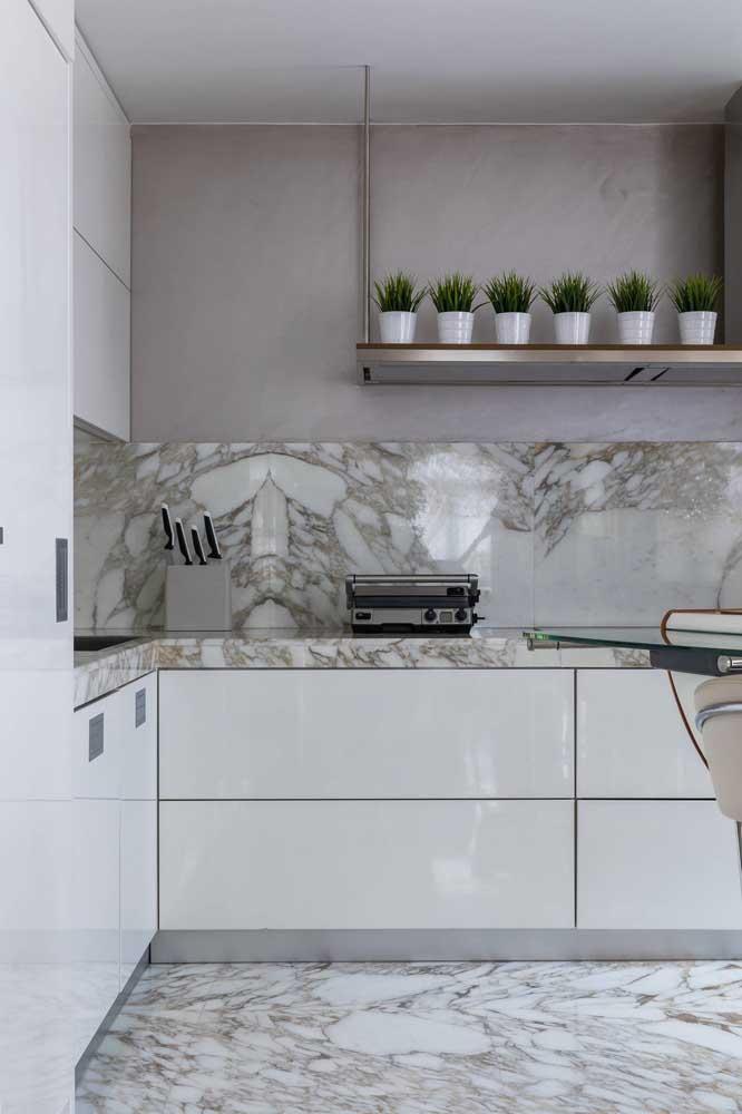 Os veios marcantes do mármore pedem por armários lisos e de aparência clean