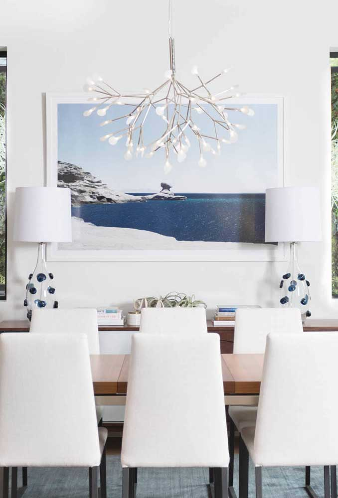 Já aqui, a moldura branca reforça o estilo elegante da sala de jantar
