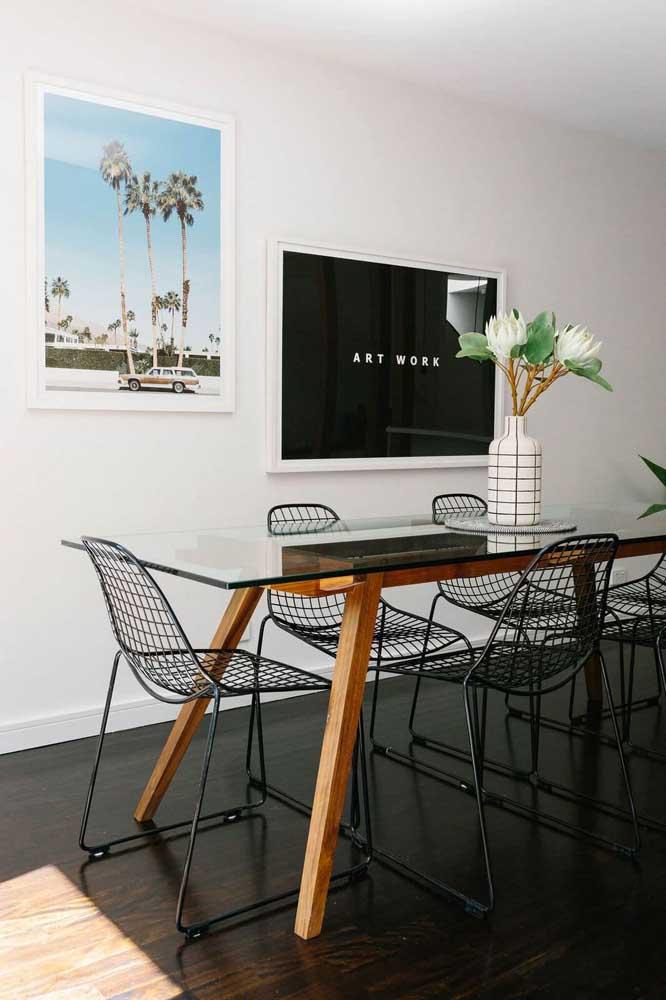 Quadros de temas variados decoram essa sala de jantar