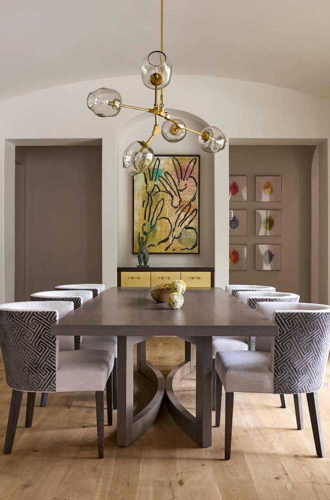 Aqui, a opção foi por um quadro grande na cabeceira da mesa. Mais aos fundos, uma composição em grade também chama atenção
