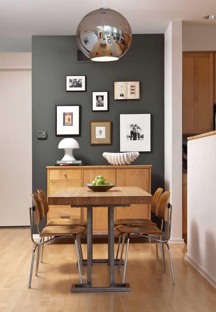 A parede preta ajuda a destacar os quadros na sala de jantar
