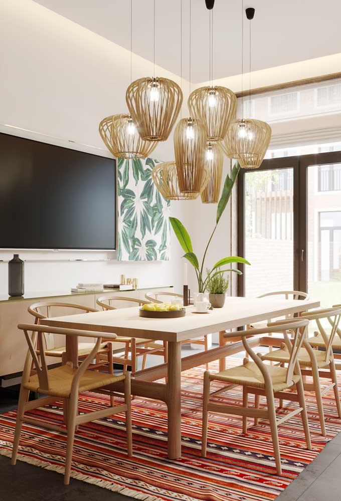 Nessa sala de jantar, o aparelho de TV divide espaço com o quadro botânico