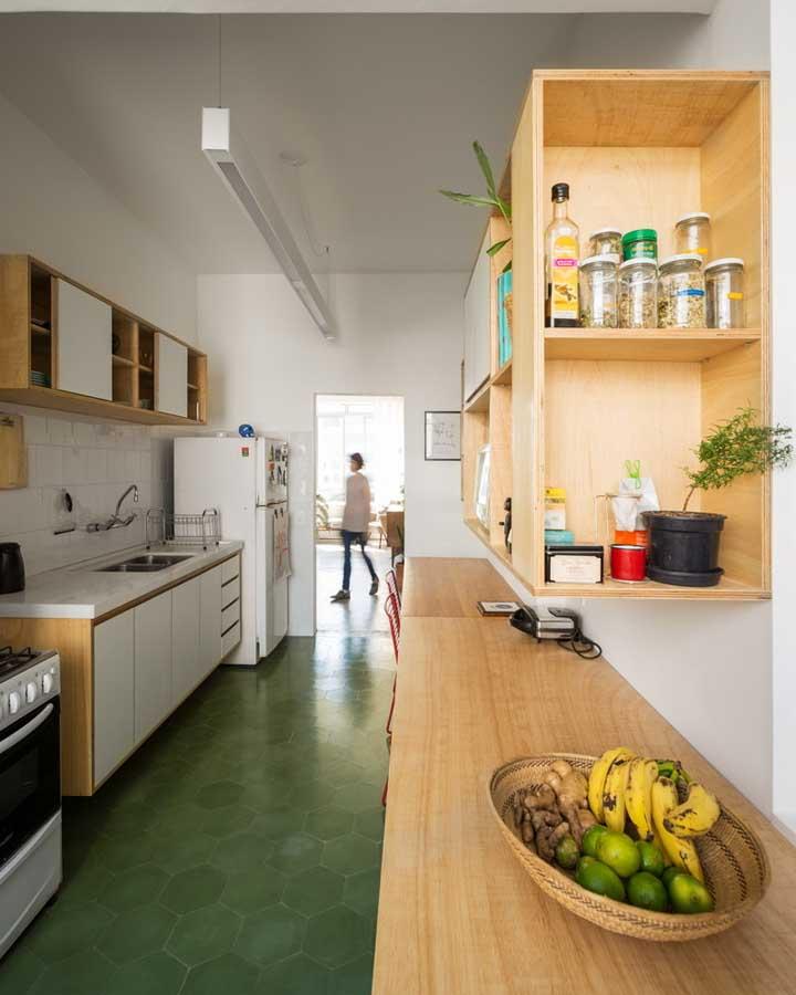 Cozinha corredor decorada com piso verde, móveis de madeira e paredes brancas