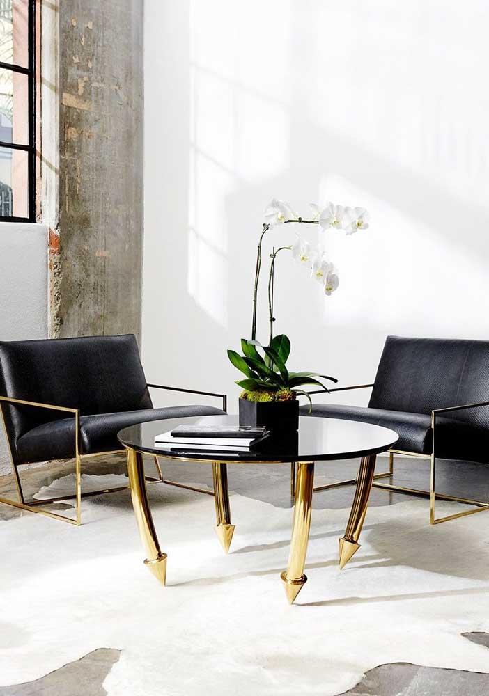 Poltrona decorativa moderna com assento de couro e estrutura metálica dourada combinando com a mesa