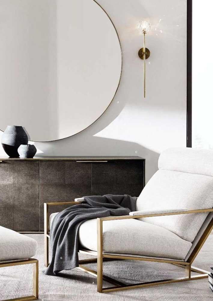 Poltrona decorativa clean e moderna com destaque para a estrutura dourada