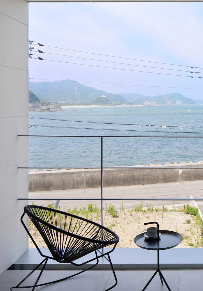 Uma poltrona confortável para apreciar a bela paisagem da varanda