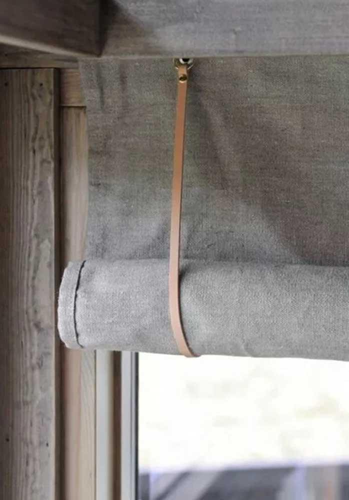 O charme dessa cortina de rolo é a tira de couro que a prende no varão