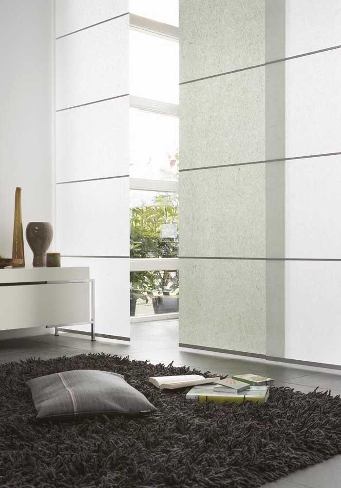 Aqui, a cortina painel é utilizada como uma divisória entre os ambientes