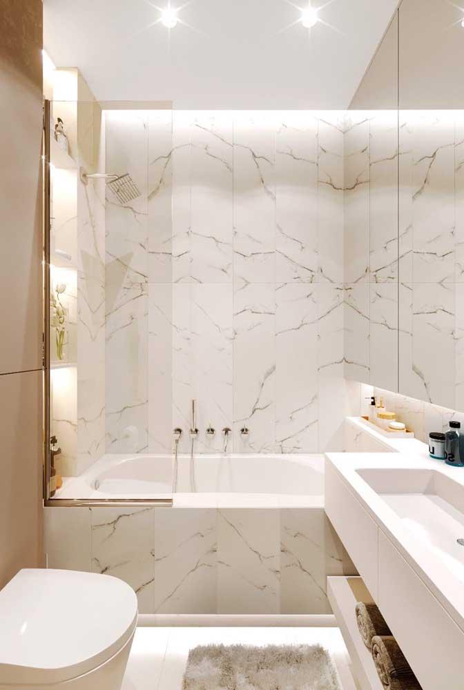 A banheira pequena ganha destaque com o revestimento de mármore e a iluminação indireta