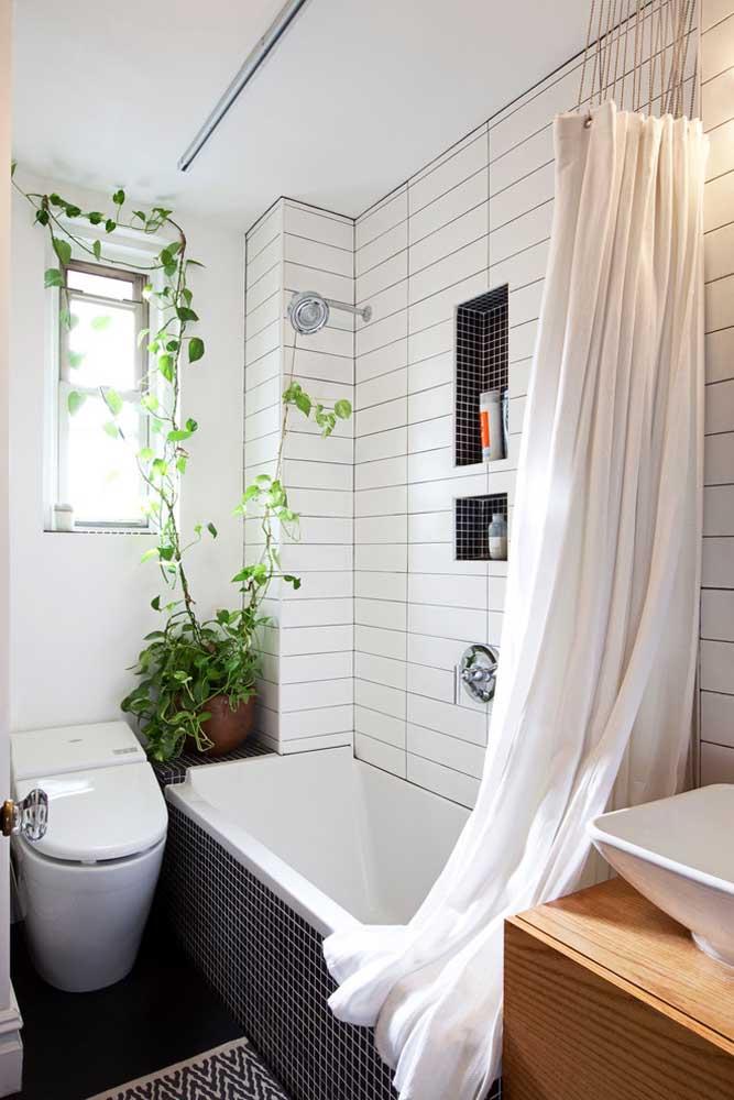 Banheira pequena retangular instalada lado a lado com o vaso sanitário e integrada com o chuveiro