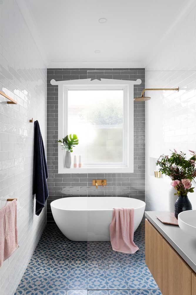 Esse banheiro pequeno traz a banheira instalada rente a janela