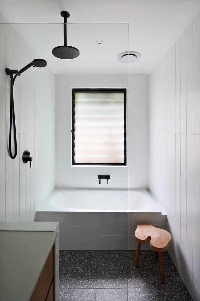Um banquinho charmoso de madeira para complementar o visual do banheiro pequeno com banheira