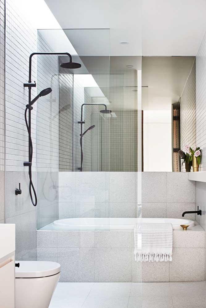 Banheira pequena retangular junto com o box. O espelho ajuda a ampliar a sensação de espaço