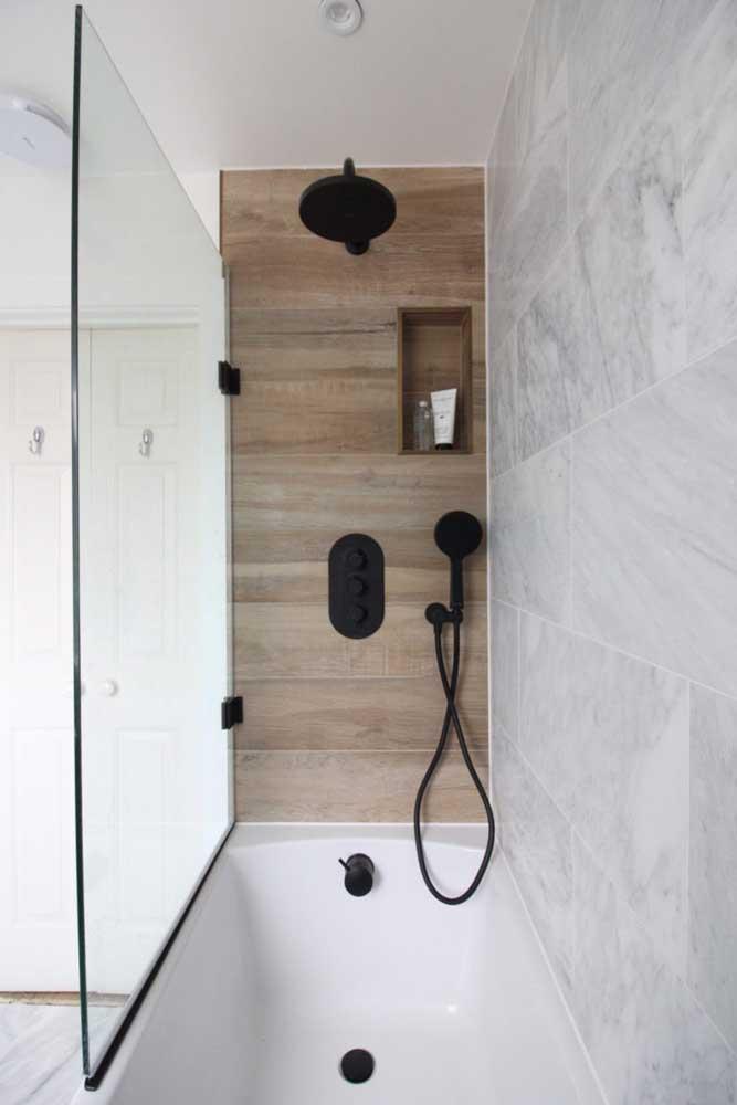 E o que acha de combinar a banheira pequena com revestimento amadeirado na parede?