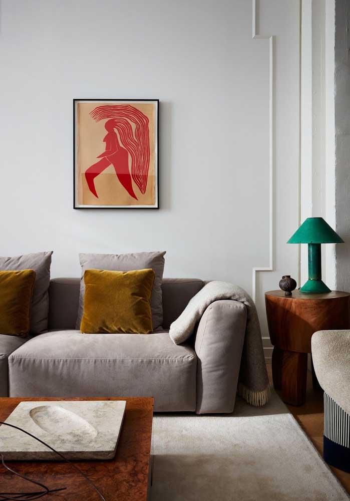 Sala decorada com sofá cinza e detalhes coloridos