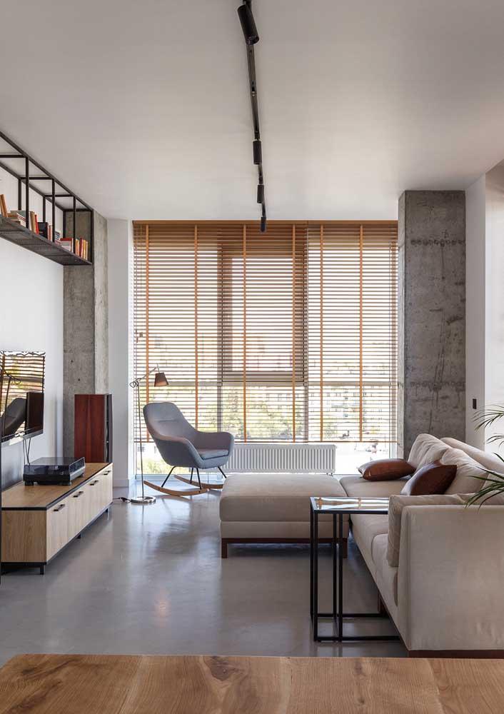 O cimento queimado e os detalhes em ferro ditam o estilo industrial nessa sala decorada de apartamento