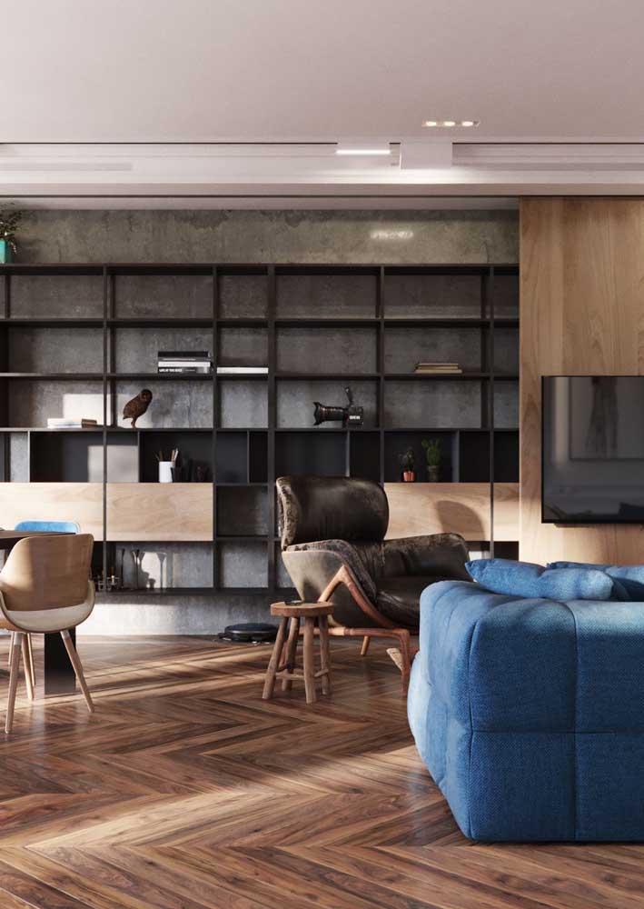 Sala integrada decorada com piso de madeira e parede de cimento queimado
