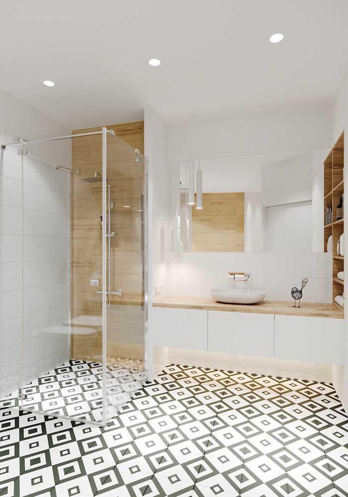 Armário branco e bancada de madeira clara para um banheiro clean e moderno