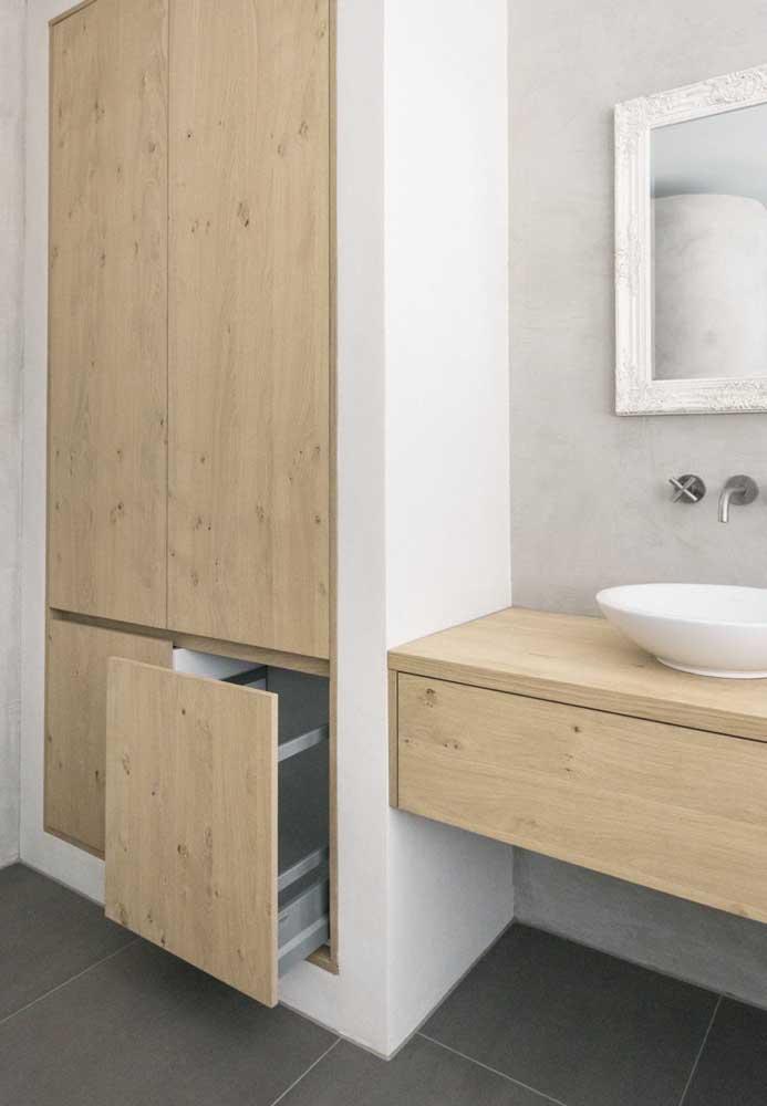 Armário de banheiro embutido com portas em madeira clara combinando com a bancada