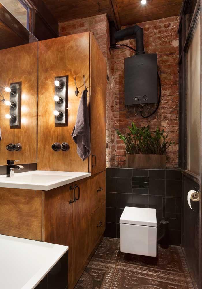 Banheiro rústico com armário de madeira maciça harmoniosamente colocado junto a parede de tijolinhos
