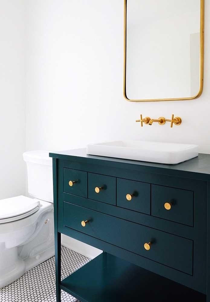 Armário antigo para banheiro em um tom de azul que é pura elegância. Destaque ainda para os puxadores dourados